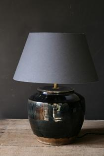 A black ceramic table lamp and grey shade