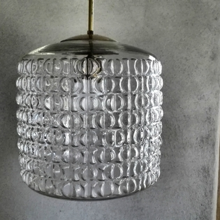 A glass pendant lamp with brass top