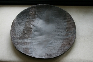 A grey and red ceramic plate.